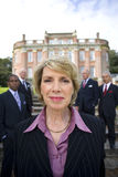 Businesswoman by colleagues in grounds of manor house, portrait, close-up royalty free stock photo