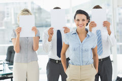 Businesswoman with colleagues holding blank paper in front of faces Royalty Free Stock Images
