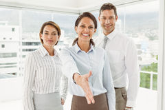 Businesswoman with colleagues offering handshake at office Royalty Free Stock Photography