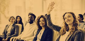 Businesswoman raising hand during meeting. Businesswoman with colleagues raising hand during meeting in office royalty free stock image