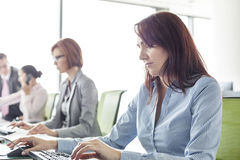 Businesswoman with colleagues working in open plan office Royalty Free Stock Photography