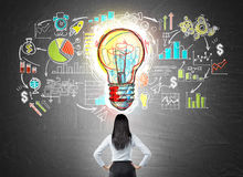 Businesswoman and colorful sketch. Rear view of businesswoman with hands on waist looking at colorful startup sketch on chalkboard with large light bulb icon in Stock Image