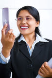 Businesswoman communicates using video call. A young Asian businesswoman is talking using video call feature in her cell-phone royalty free stock images