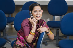 Businesswoman Communicating On Cell Phone. An Indian business women communicating on cell phone while sitting on chair in training room stock photos