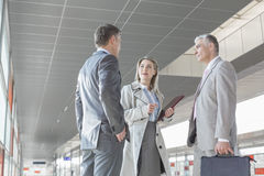 Businesswoman communicating with male colleagues on train platform Royalty Free Stock Photography