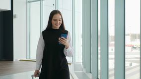 Businesswoman on commute transit talking on the smartphone while walking with hand luggage in train station or airpot. Going to boarding gate. Asian woman happy stock video