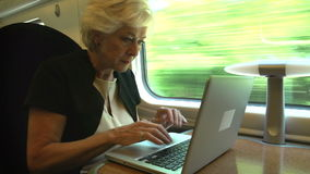 Businesswoman Commuting To Work On Train And Using Laptop. Senior businesswoman sitting at table working at laptop.Shot on Sony FS700 in PAL format at a frame stock video footage