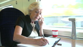 Businesswoman Commuting To Work On Train Using Mobile Phone. Businesswoman sitting at table talking on mobile phone and making notes on document.Shot on Sony stock video footage