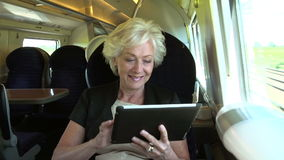 Businesswoman Commuting On Train Using Digital Tablet