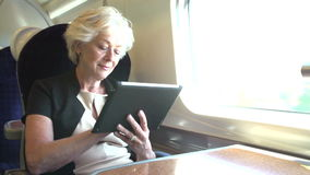 Businesswoman Commuting On Train Using Digital Tablet Royalty Free Stock Photography
