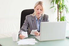 Businesswoman comparing bills Royalty Free Stock Photography
