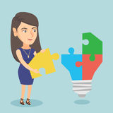 Businesswoman completing lightbulb made of puzzle. Stock Image