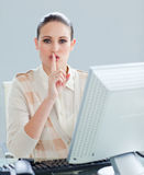 A businesswoman at a computer asking for silence Royalty Free Stock Image