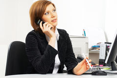 Businesswoman with computer. Business woman talking by phone in office Royalty Free Stock Image