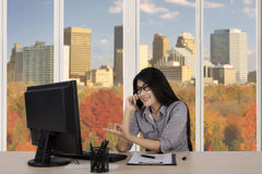 Businesswoman with computer and phone in office Royalty Free Stock Images