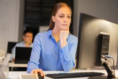 Businesswoman at computer working at night office stock images