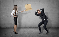 Businesswoman on concrete background holding a carton box to a cowering man. royalty free stock image