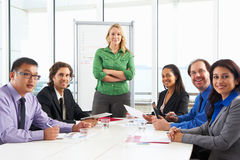 Businesswoman Conducting Meeting In Boardroom Stock Image