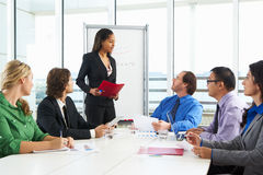 Businesswoman Conducting Meeting In Boardroom Stock Photo