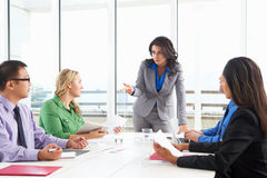 Businesswoman Conducting Meeting In Boardroom Stock Images