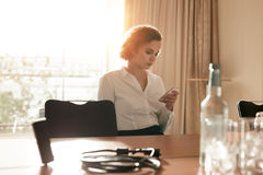 Businesswoman at conference table using mobile phone Stock Photos