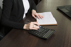 Businesswoman considers on the calculator. The woman in the workplace considers on the calculator. close up Stock Image