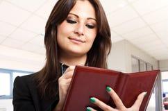 Businesswoman consulting agenda Stock Image