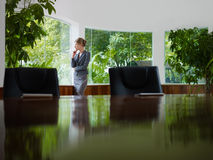 Businesswoman contemplating out of window Royalty Free Stock Image