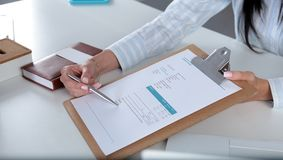 Businesswoman with contract giving pen to partner to sign it.  Royalty Free Stock Image