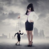 Businesswoman controlled by her boss. Businesswoman hanging on string and controlled by a businesswoman stock image