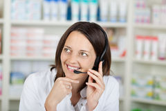 Businesswoman Conversing On Headset In Pharmacy Stock Images