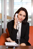 Businesswoman conversing on landline phone Royalty Free Stock Photos