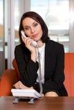 Businesswoman conversing on landline phone Stock Photography