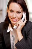 Businesswoman conversing on landline phone, portrait Royalty Free Stock Images