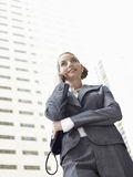 Businesswoman Conversing Mobile Phone Against Tall Office Buildi Royalty Free Stock Photo