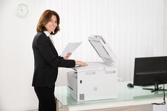 Businesswoman Copying Paper On Photocopy Machine. Smiling Businesswoman Copying Paper On Photocopy Machine In Office Stock Images