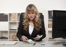 Businesswoman counting out money at her desk Stock Image