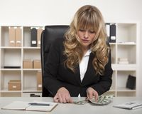 Businesswoman counting out money at her desk Royalty Free Stock Photo