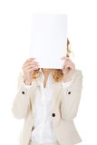 Businesswoman covering face with paper sheet. Stock Photos