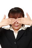 Businesswoman covering her face with hands against white background Royalty Free Stock Photography