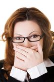Businesswoman covering her mouth because of shame.  Royalty Free Stock Photography