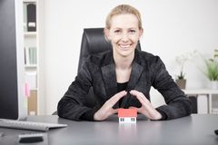 Businesswoman Covering Miniature House on Table Royalty Free Stock Images