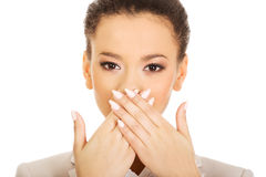 Businesswoman covering mouth with hands. Royalty Free Stock Photography