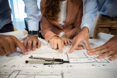 Businesswoman and coworker discussing blueprint on the desk Royalty Free Stock Photos