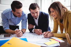 Businesswoman with coworkers discussing on blueprint Stock Photography