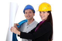 Businesswoman and craftsman looking at a blueprint. A businesswoman and craftsman looking at a blueprint Stock Photo