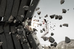 Businesswoman crashing bricks . Mixed media Royalty Free Stock Images