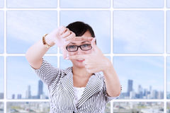 Businesswoman creating frame with fingers Stock Photo