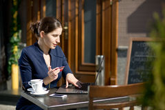 Businesswoman with credit card and laptop. Sitting at a table in a cafe on the street Royalty Free Stock Photography