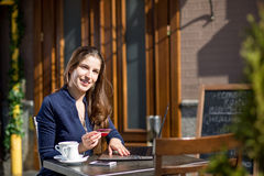 Businesswoman with credit card. And laptop sitting at a table in a cafe on the street Stock Photo